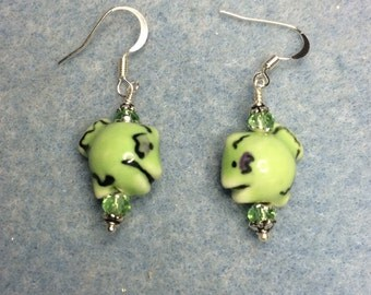 Green ceramic fish bead dangle earrings adorned with green crystal beads.