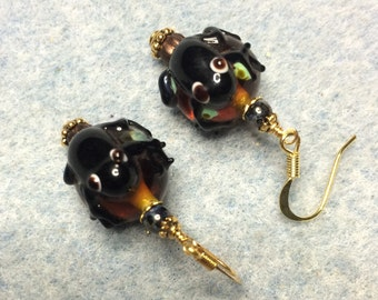 Brown and green lampwork frog bead earrings adorned with brown Czech glass beads.