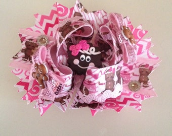 Gingerbread girl boutique hairbow with an alligator clip attached to the back.