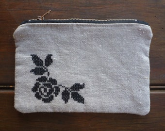 Rustic linen zippered pouch with black rose cross stitch.