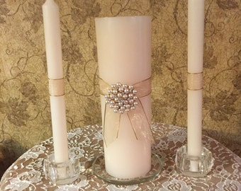 This Ivory Pillar Candle Set is Embellished with a Shimmering Ribbon and a Large Pearl and Rhinestone Pendant.  Perfect for any Wedding.