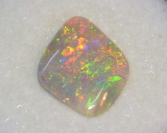 Lightning Ridge Precious Opal, grey base color freeform cut with 'RARE' pinfire over broadflash play of brilliant color