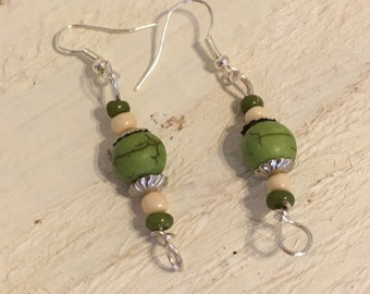 Green and Off-white dangle pierced earrings.