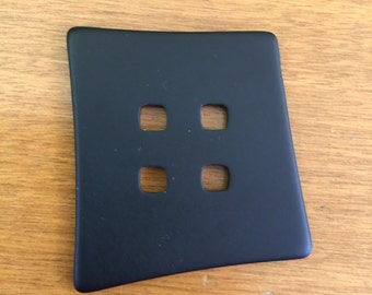 "Large black plastic button in an organic ""squarish"" shape."