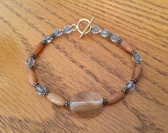 Tan Beaded Bracelet with Clear Accent Bead containing Gold Sparkles