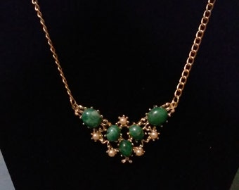 Green beaded butterfly pendant on a brass chain.