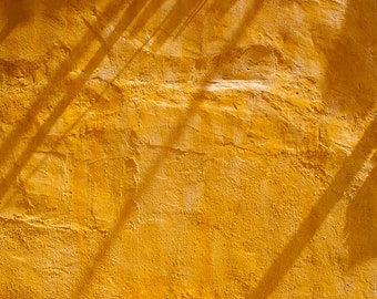 Mediterranean rustic ochre wall with sunlight and shadows, Spain