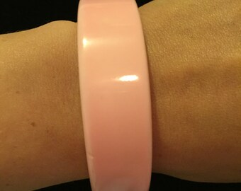 Pink cuff bracelet from pre 90's. I am not sure on the age. It could from the 50's to 80's.