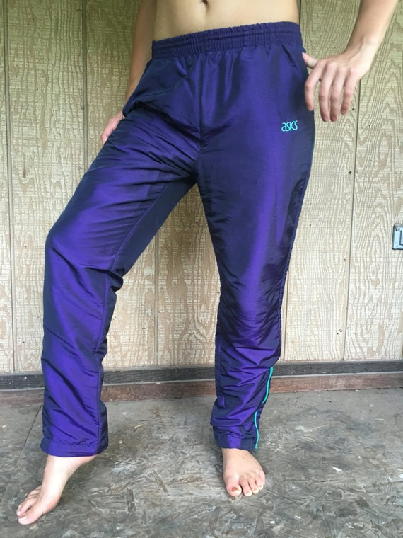 Vintage 80s iridescent ASICS jogging pants in deep plum purple with mint green detailing. Zippers on the bottom of each pant leg. Size small