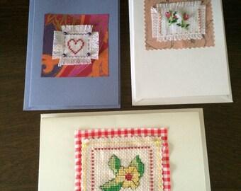 Three hand stitched cards .