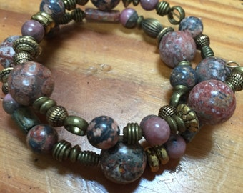 Mauve and grey beaded , memory wire bracelet accented with metal beads. One size fits all.