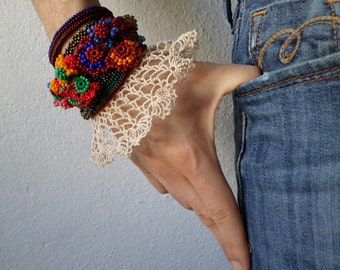 freeform crochet bracelet with colorful beaded flowers and cream crochet lace