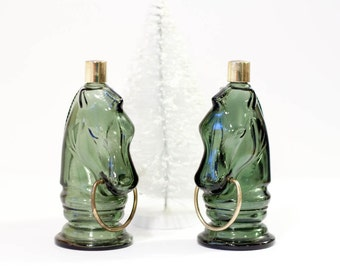 Vintage glass horse head bottles, dark green Avon horse bottles with gold lids and rings in their mouths, glass statues