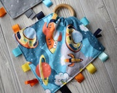 9 x 9 sensory blanket with maple teething ring, ribbons and crinkle material.  Can be personalized.