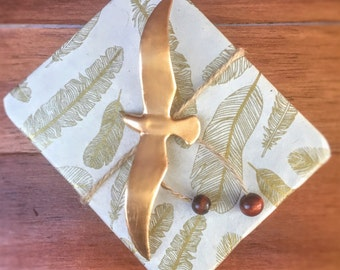 Custom Wrapping with Feather Paper, Twine with Wood Beads, and 24K Painted Seagull for Craine's Nest Product