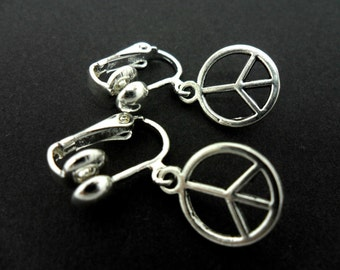 A pair of cute little tibetan silver peace sign dangly clip on earrings.