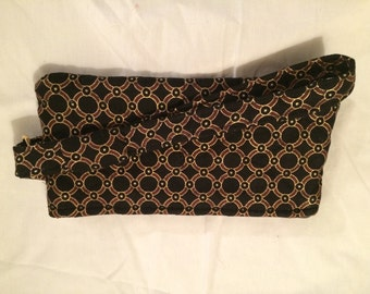 Black wristlet adorned with glittery gold rings design
