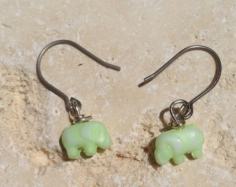Tiny pale green elephant earrings dangle from hypo allergenic titanium earring hooks