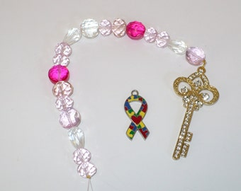 Rhinestone golden key suncatcher with crystals in hues of pink, rose and white.