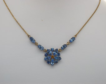 A beautiful classic 1930's / 40's period flower design vintage jewelry necklace in goldtone metal set with sparkly blue faceted glass stones