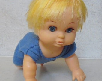 Crawling Baby Boy doll in blue romper. Blonde hair, blue open/close eyes. Right eye is a little lazy. 7""