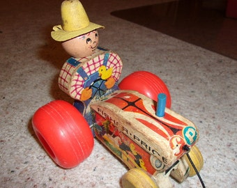 1961 Fisher Price farm tractor, pull toy,  with a bee bobbin farmer behind the wheel, # 629