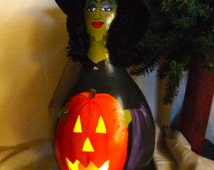 Hand crafted gourd art witch luminary with black curly hair and holding a jack o lantern by Debbie Easley