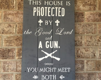 This house is protected by the Good Lord and a gun reclaimed wood sign
