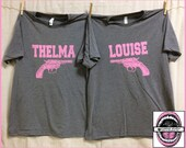 Thelma and Louise GUN image with Watch Your Mouth Buddy printed on back.Set of 2 Unisex Grey T shirt with Vintage Pink Ink. plus sizes