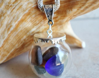 Sea glass orb necklace encloses  smooth sea glass with silver accents