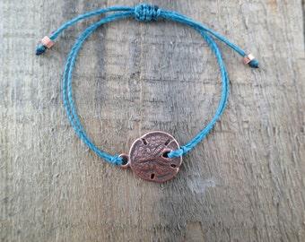 Antique Copper Sand Dollar Bracelet With Dark Teal Cord