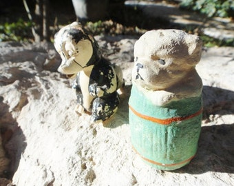 Two Chalk ware Figures Skunk and Dog in Barrell