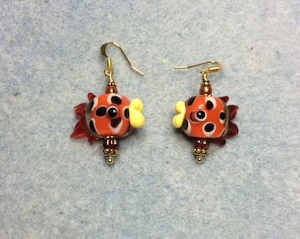 Orange and yellow lampwork fish bead earrings adorned with orange Czech glass beads.
