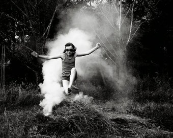 Vintage photo antique photograph girl wearing sunglasses jumping over hay fire smoke weird 1950s photo PRINT