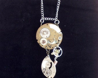 Steampunk pendant necklace featuring vintage watch parts, silver and brass findings and accent sheet metal.