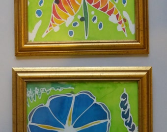 """2 batik flowers """"Morning Glory"""" & """"Star Flower"""", painted on silk. In a gold frame."""