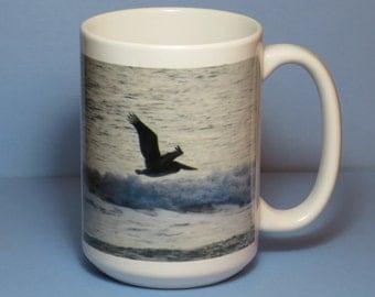 Pelican over waves at dusk - 15 oz coffee mug