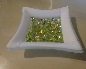 Elegant fused glass bowl with green dichroic pieces and a white rim on a clear base