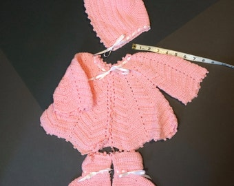 Hand crocheted infant sweater, hat, and bootie set in pink acrylic.