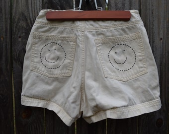 Pastel yellow shorts with smiley detail embroidered on back pockets