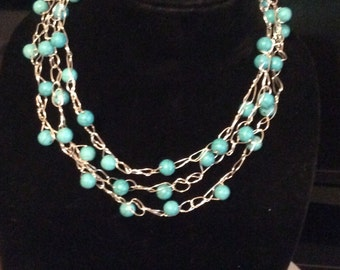 Crochet wire necklace with blue turquoise colored stones.