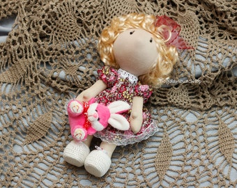 Textile soft doll in pants and dress with a toy in hands. Height 26 cm (10.7 inches). Doll for gifts and games.