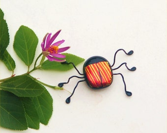 Fused dichroic glass bug in orange, yellow and red stripes