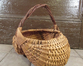 Nice woven buttocks basket with twisted stick handle- solid, beautiful, well made