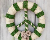 Peace sign wreath made with a burlap and green moss. With burlap roses.