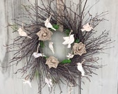 Twig wreath with Bird silhouettes cut out of white birch bark. Burlap roses in moss accents.