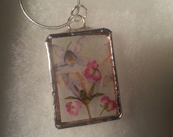 Pressed flowers in glass pendant. 2 x 2.6cms.