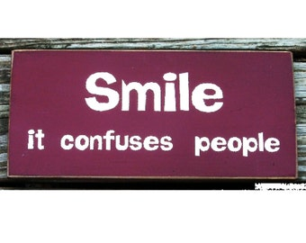 Smile it confuses people primitive wood sign