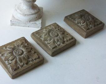 three cement leaf tiles