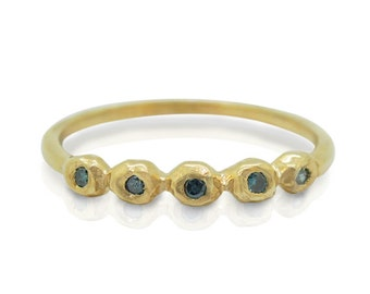 Blue diamond engagement ring set in a yellow gold band